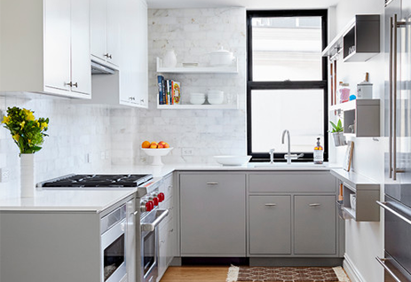 Small city apartment kitchen with light grey kitchen cabinets a Sub-Zero-Wolf range with red knobs and white painted brick walls.