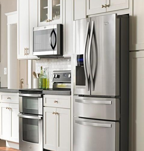 Standard-Depth Stainless Steel kitchen appliances package with OTR Microwave, dual-compartment range, and Bottom-Freezer French-Door fridge win a white kitchen with black countertop.