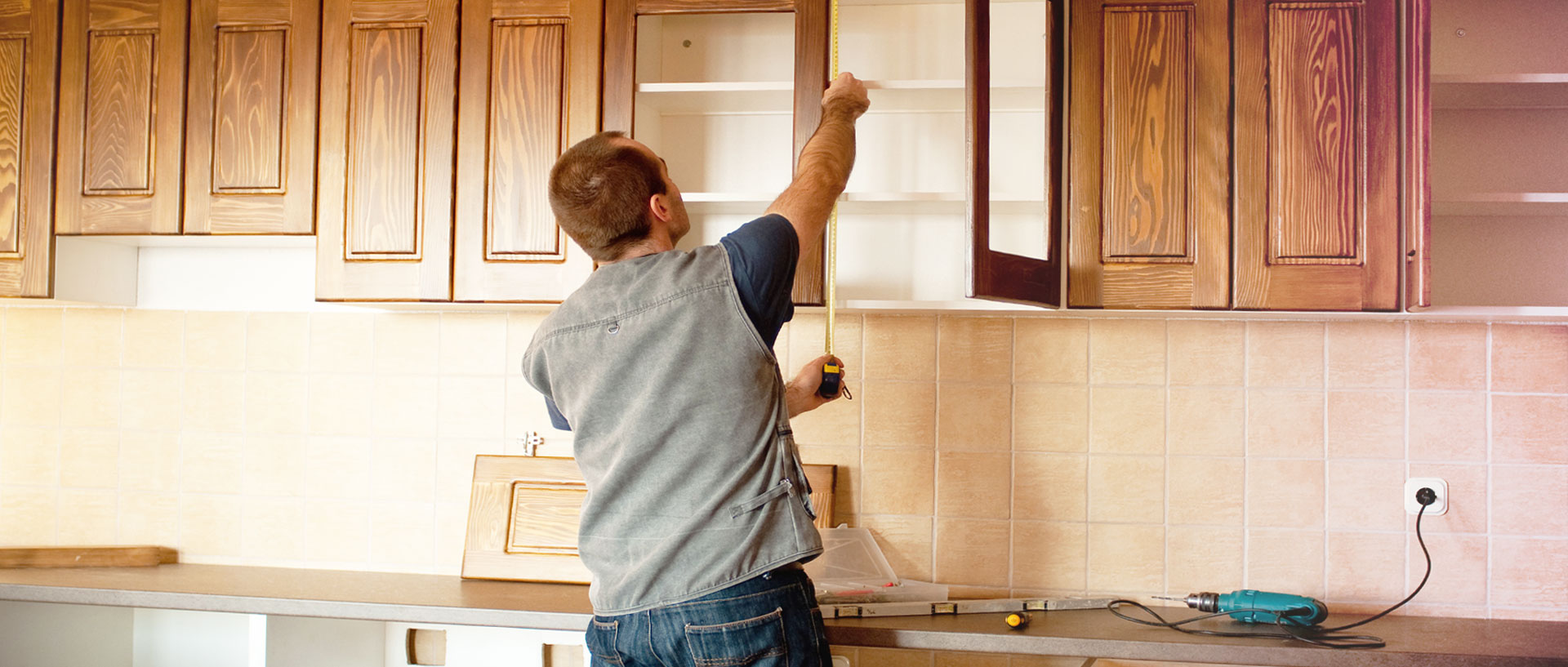A man installing country-style woodgrain cabinets in a kitchen.