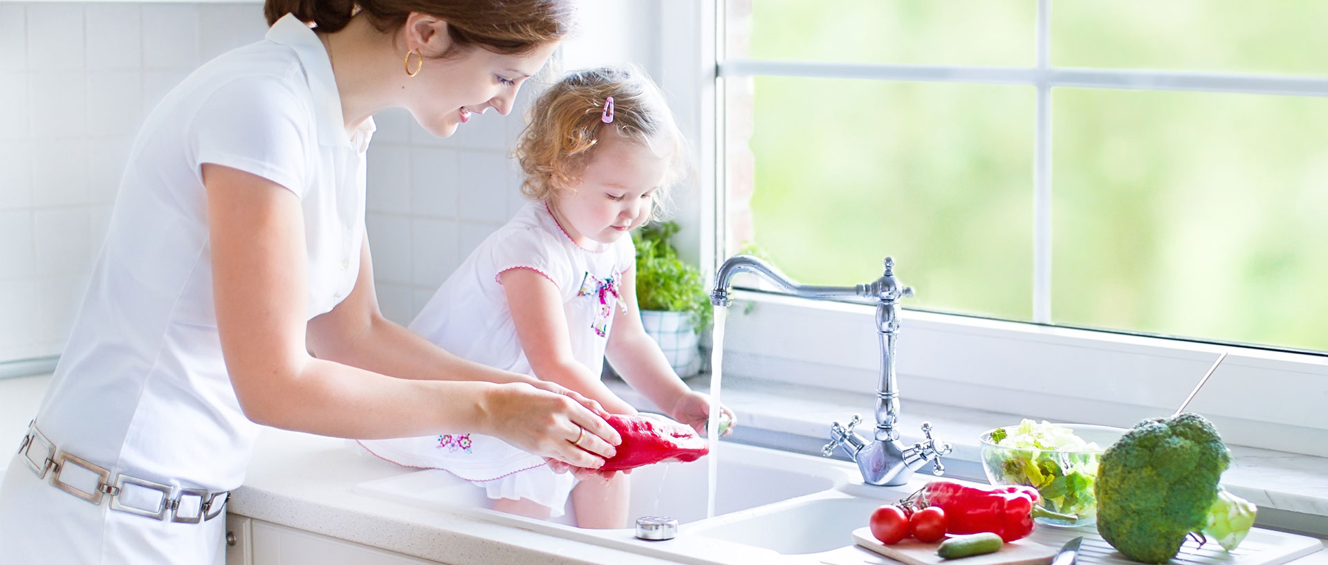 A mother and her young daughter washing vegetables in their kitchen sink.